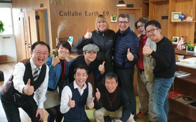 Ulrike und Andreas Dolle posieren mit dem Team von Collabo Earth e9 und, typisch japanisch, anderen Anwesenden. Den Hintergrund bildet die zentrale Kücheninsel und Kaffeee-Bar des Coworking Space